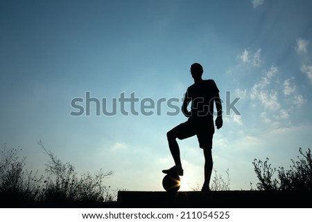 Silhouette of soccer man resting with foot on ball
