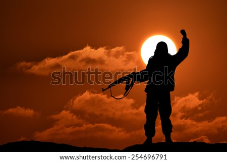 Silhouette of soldier or officer with weapons at sunset - stock photo