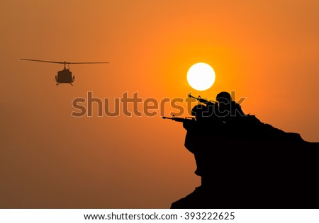silhouette of soldier shooting with flight helicopter on sunset. - stock photo