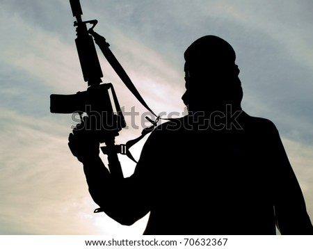 Silhouette of soldier with rifle - stock photo