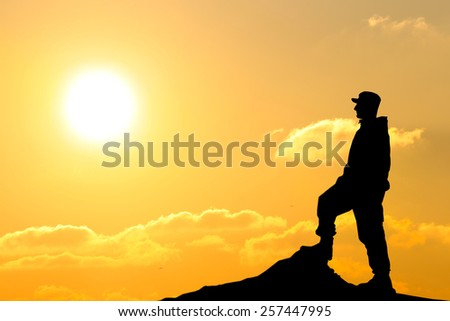 Silhouette of soldier with rifle against a sunset - stock photo