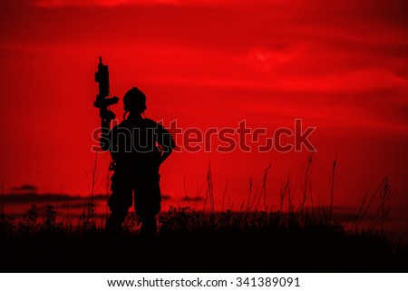 Silhouette of soldier with rifle on a red background - stock photo