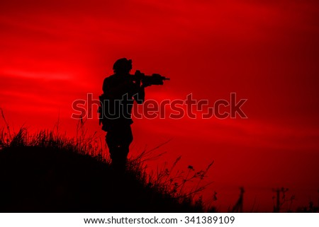 Silhouette of soldier with rifle on a red background