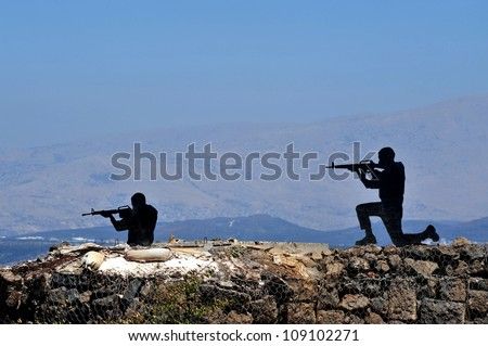 Silhouette of soldiers shooting in Mount Bental in the Golan Heights, Israel. - stock photo