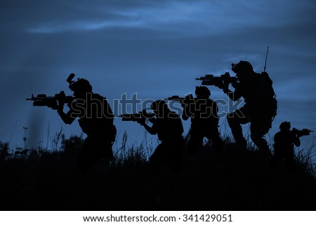 Silhouette of soldiers with rifle on a dark blue background - stock photo