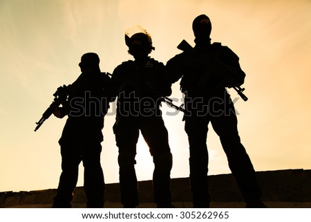 Silhouette of special forces operators with weapons - stock photo