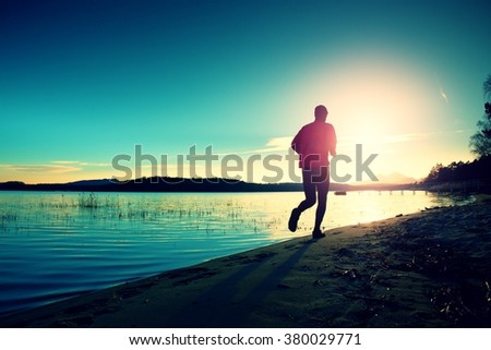 Silhouette of sport active man running and exercising on the beach at sunset. Vintage Style Toned effect - stock photo