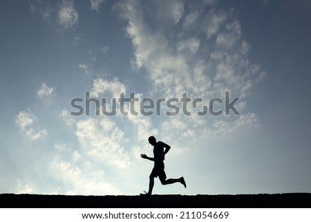 Silhouette of sport man running with blue sky and clouds on background