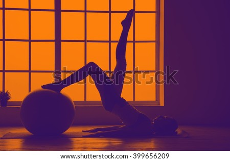Silhouette of sport woman. Woman doing the fitness ball exercises. Fitness ball. Orange violet toning image. - stock photo