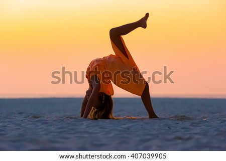 Silhouette of sporty little girl on white beach at sunset