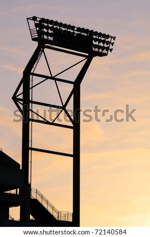Silhouette of Stadium Floodlights against a fiery sky.