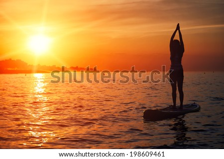 Silhouette of standup paddle board yoga performed by beautiful girl on the bright sunset background,  evening sup yoga meditation - stock photo