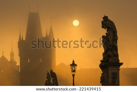 Silhouette of statue on Charles bridge during sunrise with a tower in background - stock photo