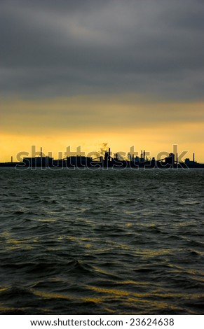 Silhouette of steel industry in Hamilton, Ontario, Canada against a yellow sky and dark clouds in front of water with waves reflecting yellow. - stock photo