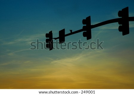 Silhouette of stoplights against sunset - stock photo