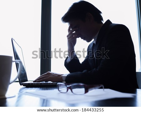 Silhouette of stressed business man in the office. - stock photo