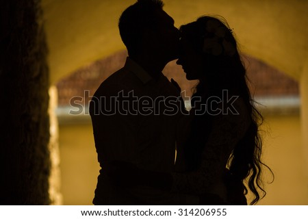 silhouette of stylish gorgeous happy brunette bride and elegant groom kissing on the background of an old wall - stock photo