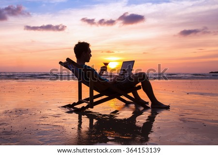 silhouette of successful business man reading emails on laptop on the beach at sunset, freelance job concept, work abroad - stock photo