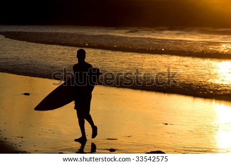 Silhouette of surfer at a yellow sunset - stock photo