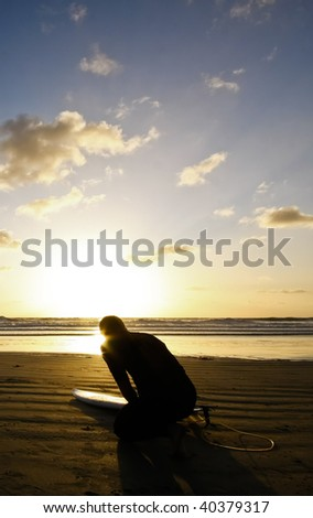 silhouette of surfer at sunset - stock photo