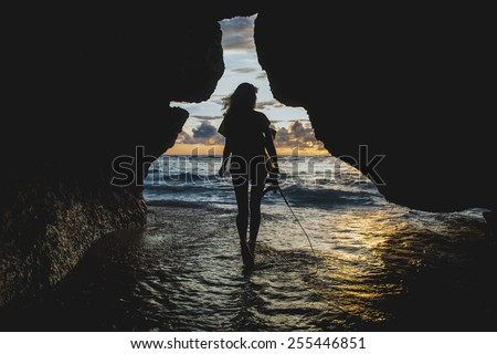 Silhouette of surfer girl who going to the sea with her short board at sunset - stock photo