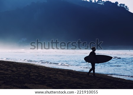Silhouette of surfer going to the water, surfer man carrying his surfing board, surfer in wetsuit holding a surfboard, surfer walking on the beach touching waves - stock photo
