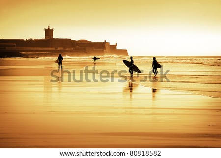 Silhouette of surfers walking in the beach at sunset - stock photo