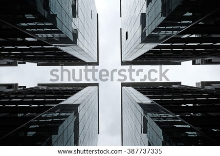 Silhouette of symmetrical glass towers on a cross road.  - stock photo