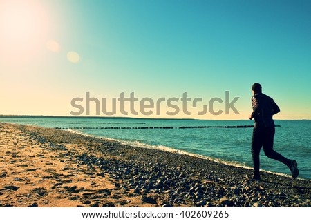Silhouette of tall man in black running  and exercising on stony beach at breakwater. Vivid and strong vignetting effect