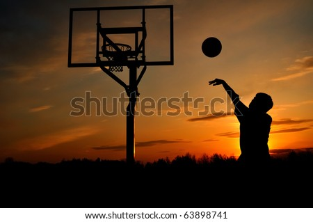 Silhouette of Teen Boy Shooting a Basketball at Sunset, copy space - stock photo