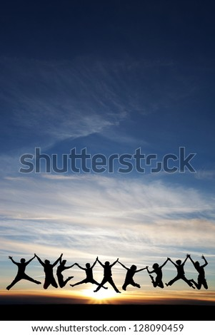 silhouette of teenagers jumping in sunset for fun - stock photo