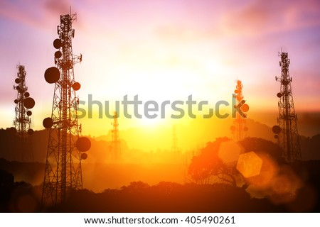 silhouette of Telecommunication mast television antennas on sunset and flare light - stock photo