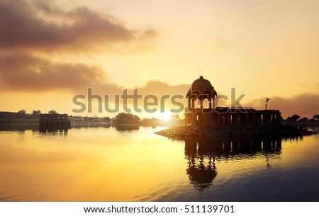Silhouette of Temple on the Gadi Sagar lake at yellow sunset sky in Jaisalmer, Rajasthan, India