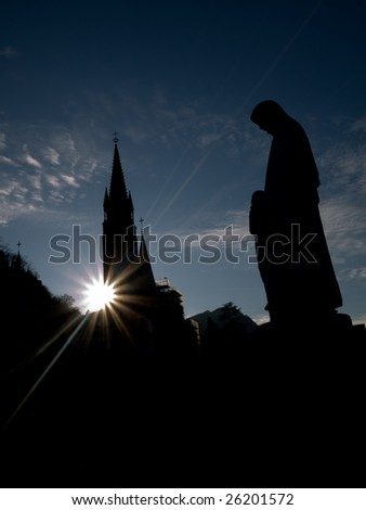 Silhouette of the Basilica of the Immaculate Conception in Lourdes with statue of the virgin Mary - stock photo
