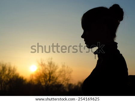 Silhouette of the beautiful girl in the nature at summer sunset. - stock photo