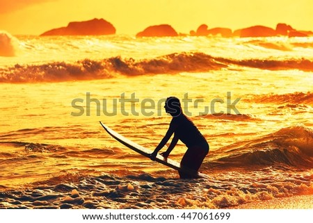 Silhouette of the beautiful surfer girl is enjoying vacation on the tropical beach. Young woman with surfboard at golden sunset. Sri Lanka. - back lit - stock photo