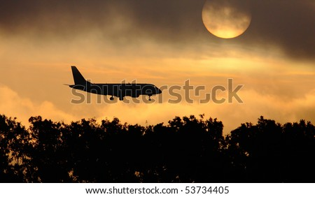 Silhouette of the big plane landing on a sunrise background. - stock photo