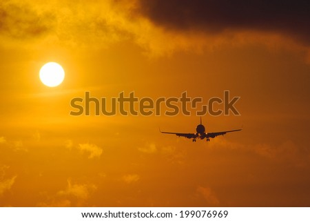 Silhouette of the big plane on a sunset background - stock photo