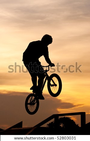 Silhouette of the boy playing Bicycle Stunts
