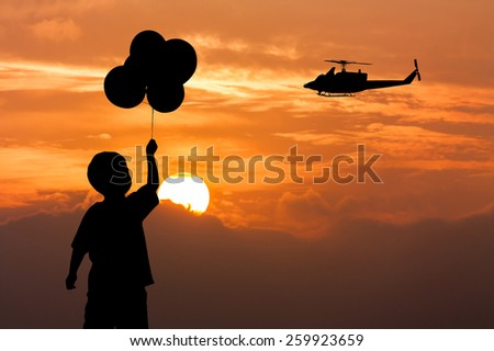 Silhouette of the boy standing and  hand holding bubble on sunset and the helicopter fly on sky