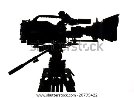 Silhouette of the camera and tripod. - stock photo