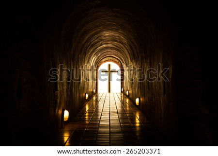 Silhouette of the cross at the end of tunnel. - stock photo
