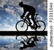 silhouette of the cyclist riding a road bike at sunset - stock photo
