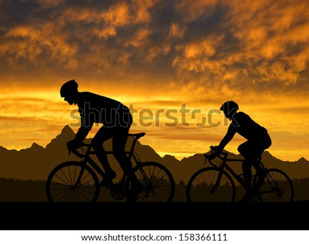 silhouette of the cyclists riding a road bike at sunset  - stock photo