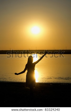Silhouette of the dancing girl with sunset on the background - stock photo
