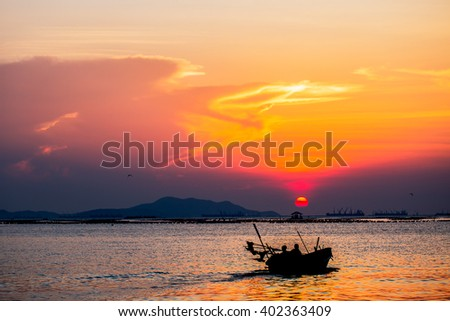 Silhouette of the fisherman boat is going to the ocean at the sunset time with the sun in background (Selective Focus Point)