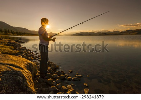 Silhouette of the fisherman on a background of lake and mountains. - stock photo