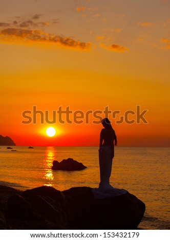 Silhouette of the girl on background rising sun