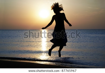 Silhouette of the happy woman jumping and dancing at the sea during sunset. Natural light and shadows - stock photo