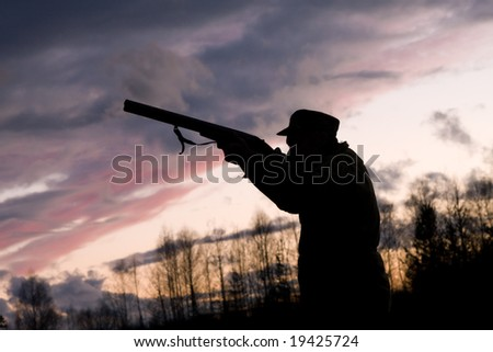 Silhouette of the hunter on a background of a morning dawn - stock photo